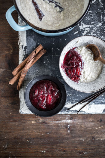 Berry Fruit Bowl Crockery Dessert Directly Above Eating Utensil Food Food And Drink Freshness Fruit Healthy Eating High Angle View Indoors  Kitchen Utensil No People Plum Plum Compote Rice Pudding Seed Spoon Sweet Food Table Temptation Wellbeing Wood - Material