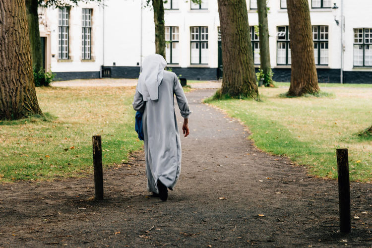 Rear view of nun walking at park