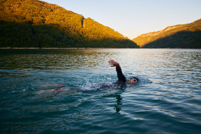 Person swimming in lake against sky