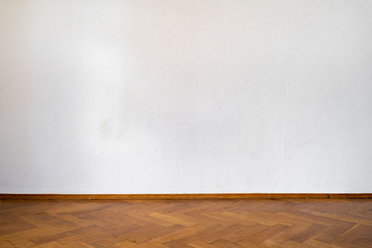 View of white wall of hardwood floor
