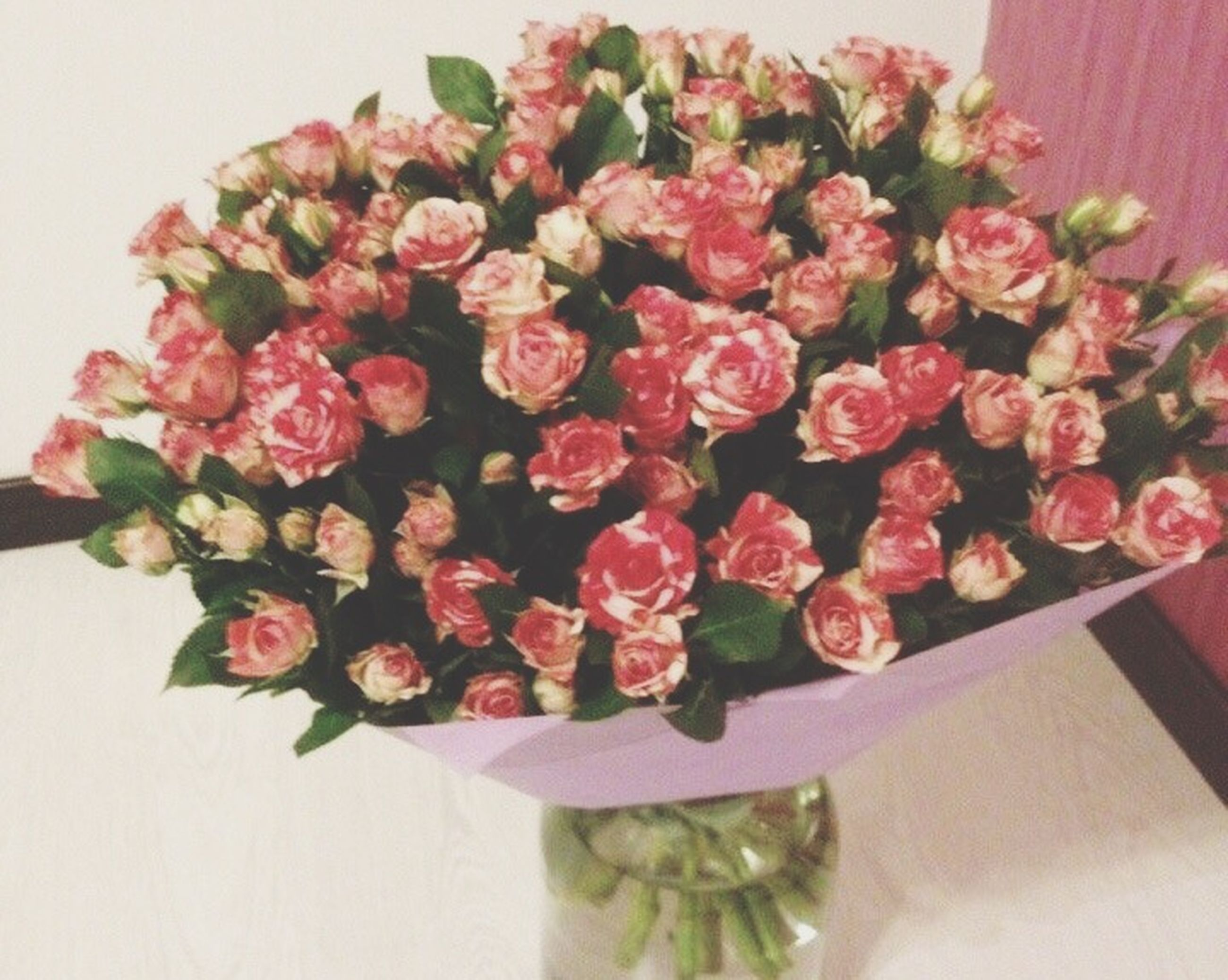 indoors, flower, freshness, table, decoration, vase, still life, home interior, close-up, bouquet, fragility, petal, flower arrangement, high angle view, no people, bunch of flowers, wall - building feature, red, pink color, variation