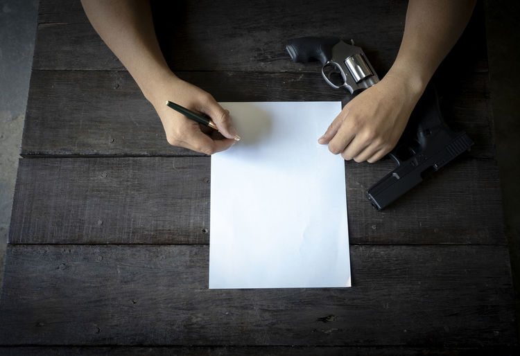 Close-up of businessman writing in paper with gun on table