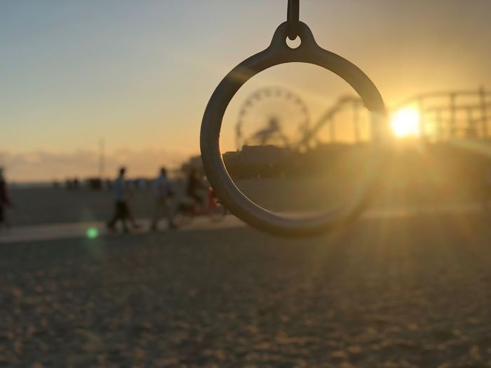 ⭕️ Santa Monica Sand Object Roller Coaster Beach Ferris Wheel California Sunset Sky Focus On Foreground Close-up Nature Lens Flare Shape Sunlight Outdoors Sun Orange Color Circle Clear Sky Lifestyles Real People
