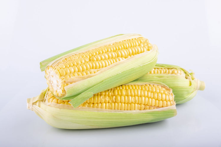 fresh raw sweet corn on the cob kernels over white background Food And Drink Vegetable Studio Shot Food Wellbeing Freshness Corn Healthy Eating Still Life White Background Indoors  Yellow Raw Food Corn On The Cob Green Color Close-up Sweetcorn No People Cut Out High Angle View Vegetarian Food