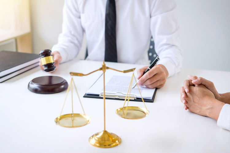 Midsection Of Lawyer Sitting By Client At Office