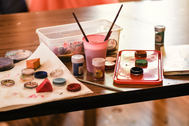 Paining  Table Brush Indoors  Paintbrush Still Life No People Palette Choice Glass Variation Paint Close-up Focus On Foreground Art And Craft Group Of Objects Drinking Glass High Angle View Watercolor Paints Group Container Art And Craft Equipment Tray