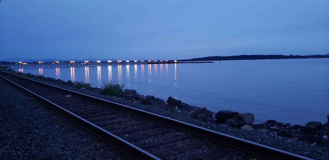 Railroad tracks against sky at night