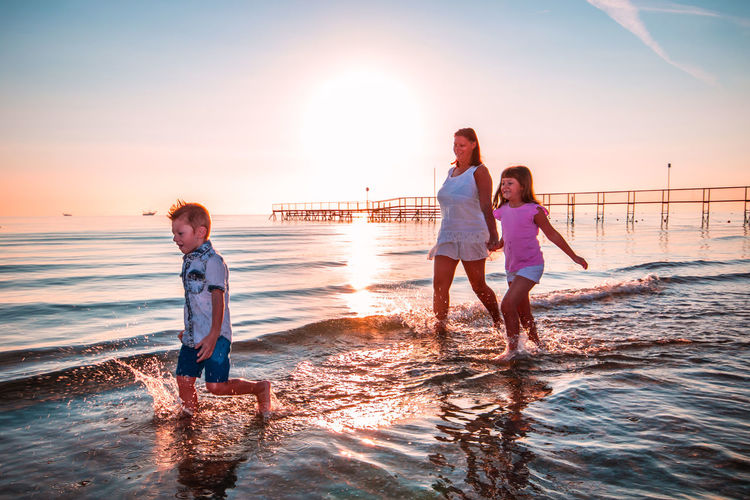 Mother with children walking in sea on shore at beach during sunset