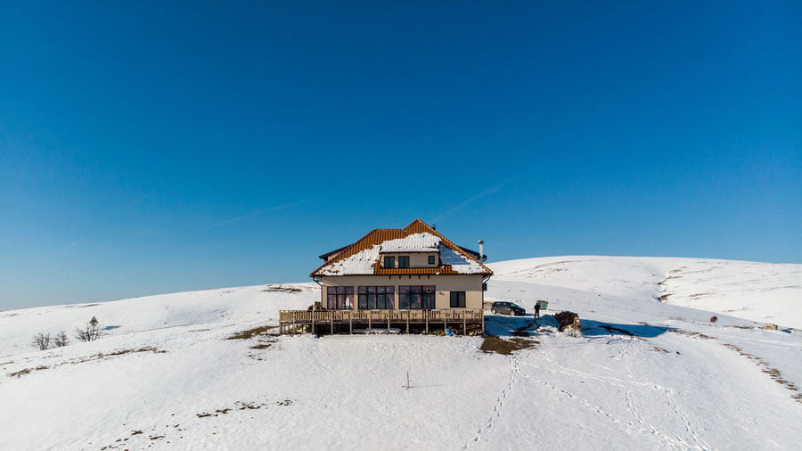 Sky Architecture Snow Blue Winter Scenics - Nature Built Structure Building Exterior Cold Temperature Clear Sky Nature Copy Space Land Building Day Tranquil Scene Beauty In Nature Landscape Hut No People Outdoors Snowcapped Mountain Cottage
