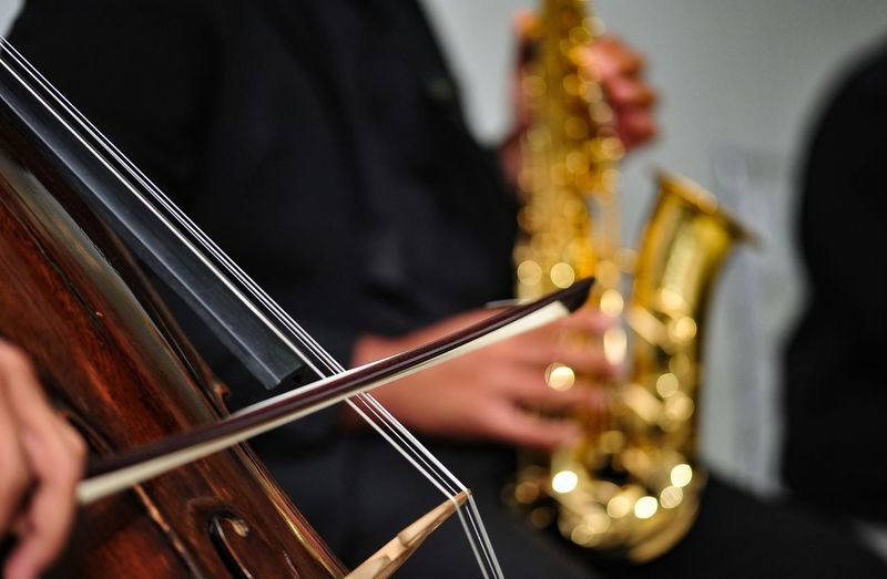 Cropped Image Of People Playing Violin And Saxophone