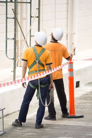 Architecture Built Structure Construction Industry Construction Site Construction Worker Coworker Development Full Length Hardhat  Hat Headwear Helmet Industry Men Occupation Outdoors Protection Protective Workwear Safety Security Standing Teamwork Two People