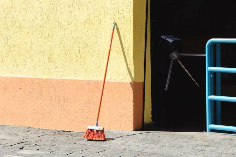 Broom on footpath against wall