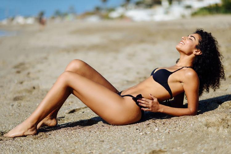 Side view of young woman wearing bikini while lying at beach
