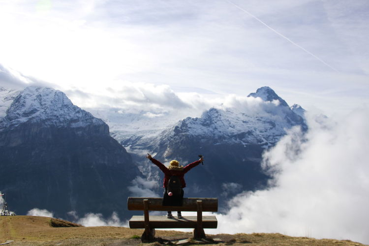 Rear view of woman sitting on bench against snow covered mountains and sky
