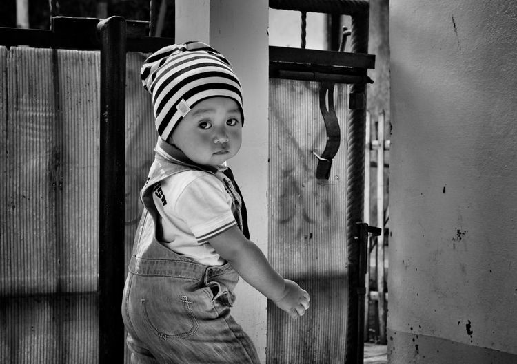 Side view portrait of baby boy standing by gate