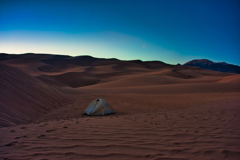 Scenic view of tent in sand dunes