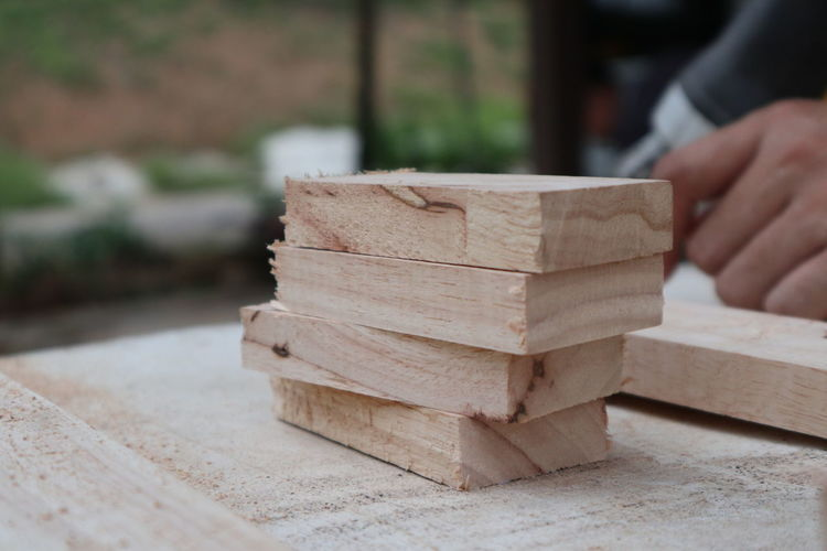 Midsection of man sitting with stacked wooden blocks on table