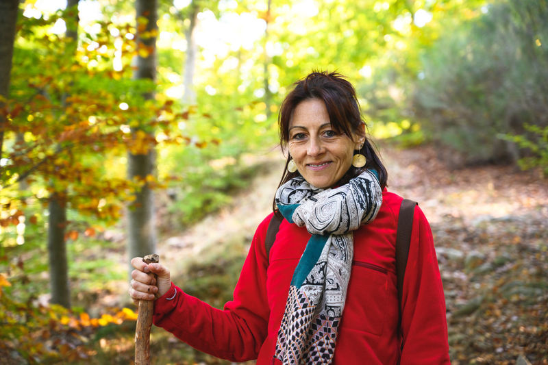 Portrait of smiling woman in forest during autumn