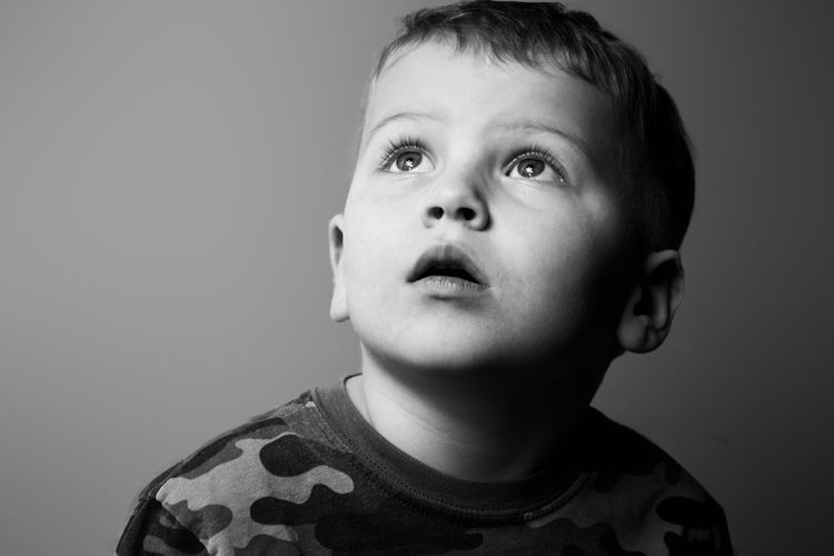Portrait of boy looking away against gray background