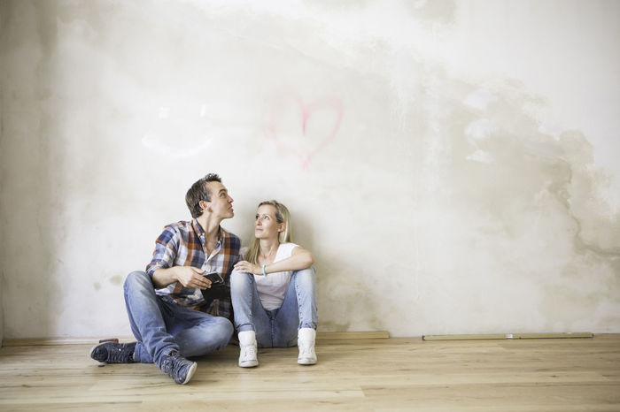Man and woman sat before a heart on a wall Casual Clothing Cloud - Sky Day DIY Friendship Grafitti Heart Leisure Activity Lifestyles Relaxation Sitting Wall