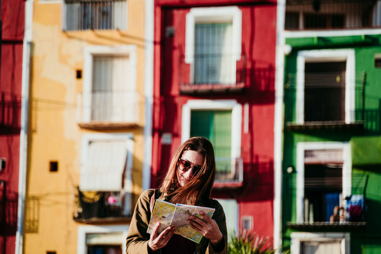 Smiling woman wearing sunglasses standing against buildings