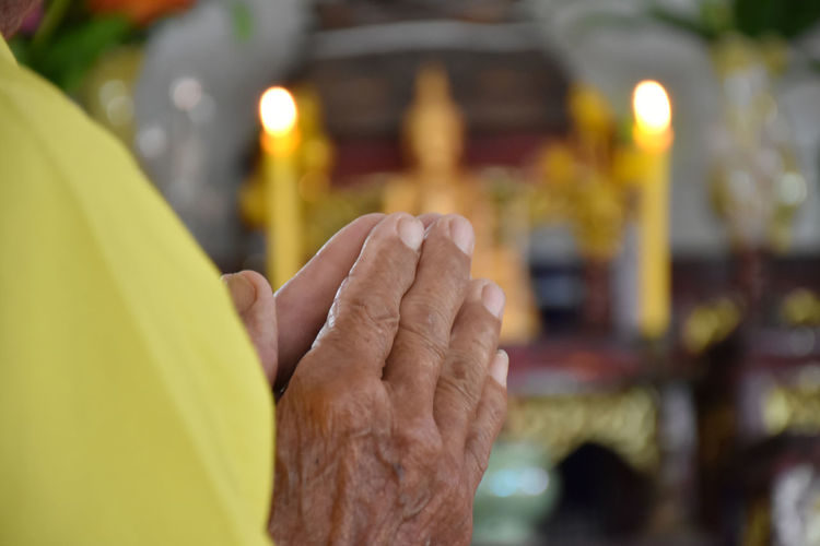 Close-up of human hand against yellow temple