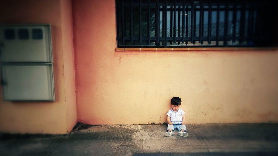 Cute boy sitting on sidewalk against house