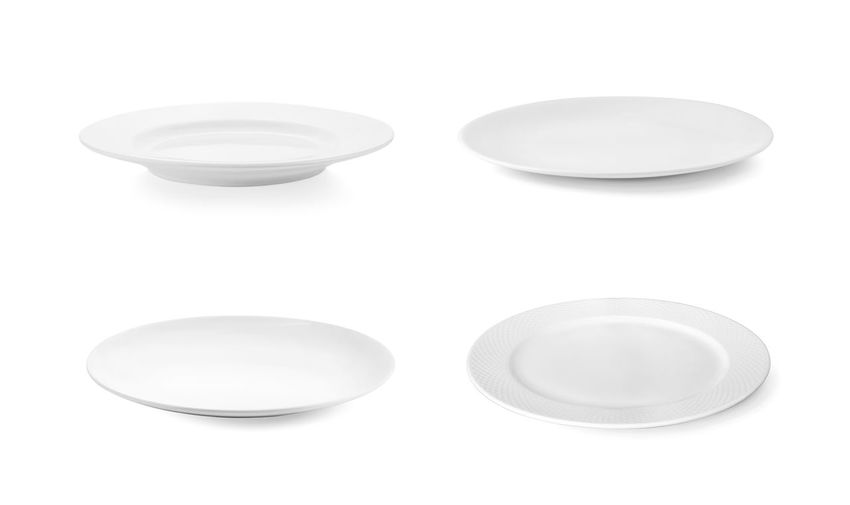 Close-up of empty plates against white background