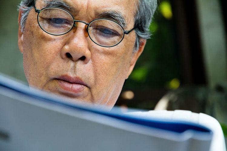 Close-up of senior man reading book