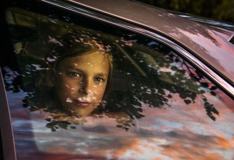 Close-up portrait of a boy in car