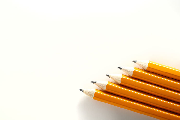 High angle view of colored pencils against white background