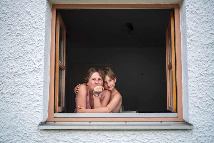 Portrait of smiling mother and son at window of house