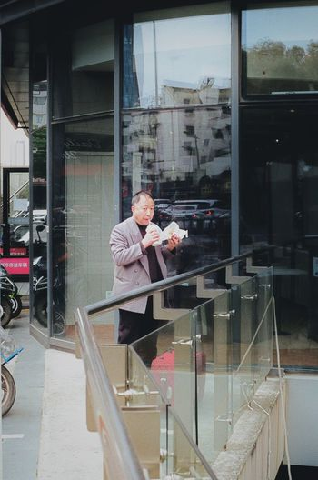 Man holding glass window of store