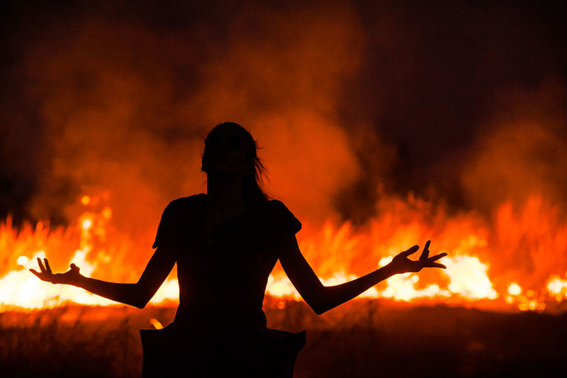 Rear View Of Silhouette Woman With Arms Outstretched In Front Of Fire On Field