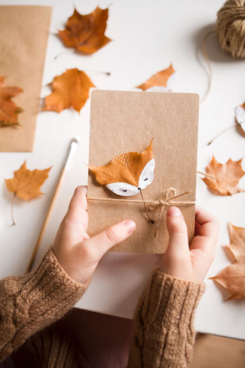 Midsection of woman holding autumn leaf on table