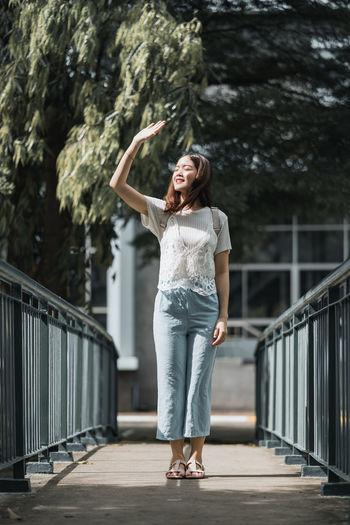 Full length of smiling standing on footbridge