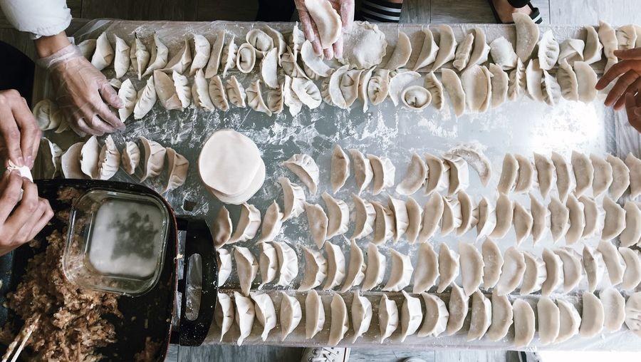 Cropped hands of people making dumplings in kitchen