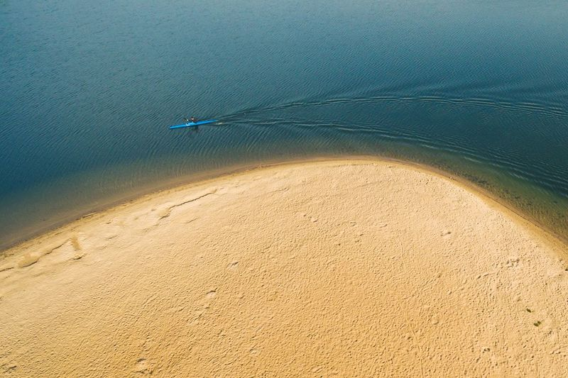 High Angle View Of Person Canoeing In Sea By Beach