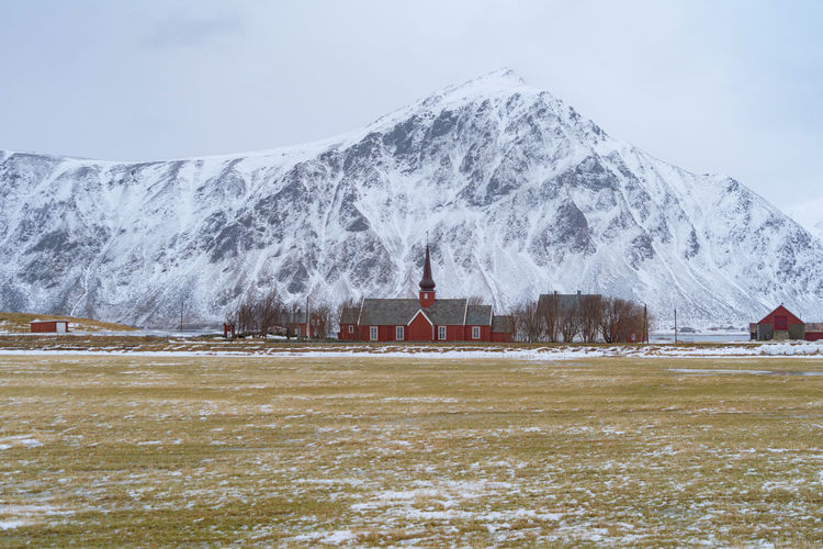 Church by on snowcapped mountain against clear sky
