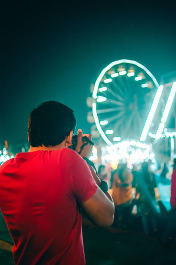 Arts Culture And Entertainment Amusement Park Illuminated Night Rear View Amusement Park Ride Ferris Wheel Real People Men Leisure Activity People Standing Lifestyles Motion Casual Clothing Waist Up Adult Dancing Outdoors
