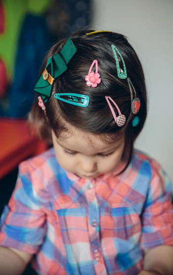 Close-up of cute girl wearing various hair clip while sitting at home