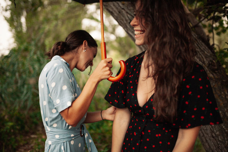 Young lesbian couple holding umbrella in the forest