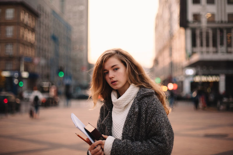 Portrait of young woman using phone on street in city