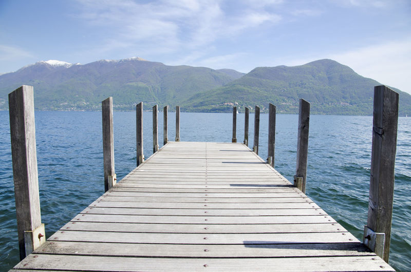 Pier on alpine lake Maggiore with mountain in Ticino, Switzerland. Alpine Lake Beauty In Nature Boardwalk Day Diminishing Perspective Idyllic Jetty Lake Maggiore Long Mountain Mountain Range Nature No People Outdoors Pier Scenics Sky Blue Sunny The Way Forward Tranquil Scene Tranquility Vanishing Point Water Wood Wood - Material