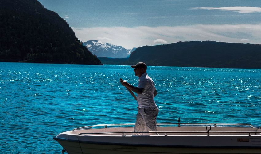 Man standing in boat on sea against mountains