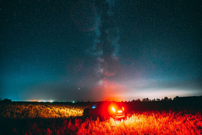 Scenic view of illuminated field against sky at night