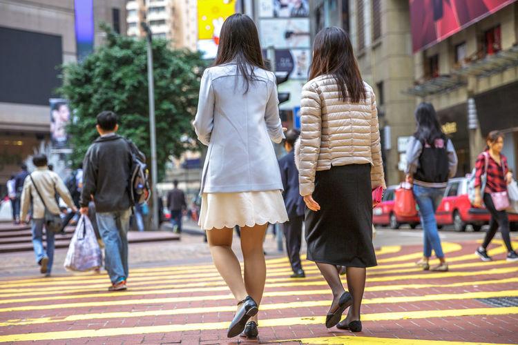 Rear view of women walking on zebra crossing