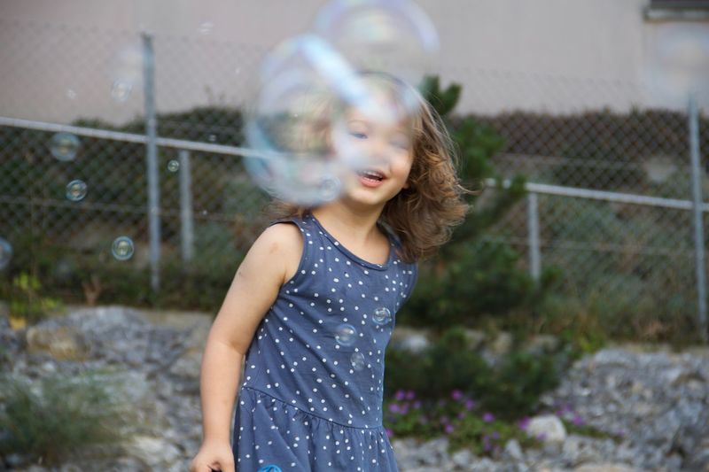 Girl standing by bubbles outdoors