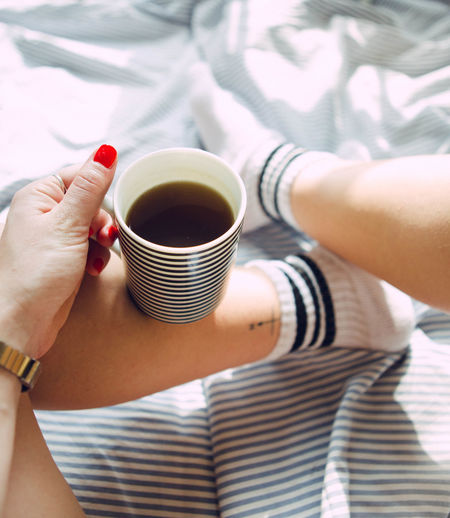 Personal perspective of woman holding coffee cup on bed