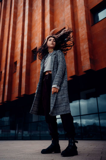 Full length of young woman standing against building in city